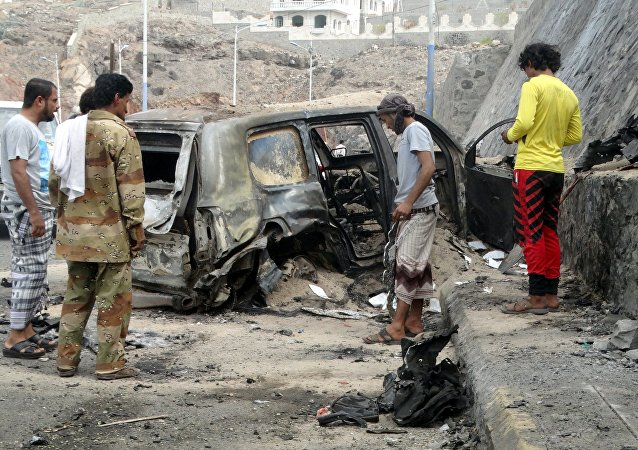 People look at the wreckage of a car at the site of the a car bomb attack that killed the governor of Yemen's southern port city of Aden December 6, 2015