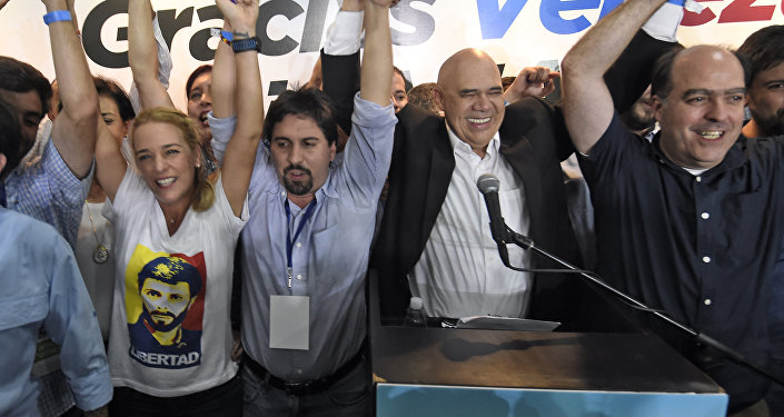 (L to R) The wife of jailed Venezuelan opposition leader Leopoldo Lopez, Lilian Tintori (C) Freddy Guevara, of the Voluntad Popular party, Jesus Torrealba, head of the Democratic Unity Movement (MUD) party and deputy Julio Borges celebrate after knowing the first results of the legislative election, at the MUD headquarters in Caracas, on the early morning December 7, 2015.