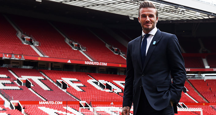 Former Manchester United and England footballer David Beckham poses on the pitch at Old Trafford in Manchester, north west England on October 6, 2015 ahead of a charity football match in aid of UNICEF