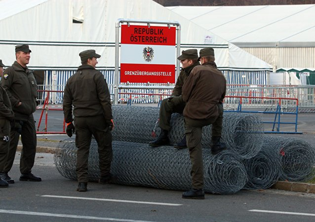 Austrian soldiers stand next to rolls of fence at the border between Slovenian and Austria in Spielfeld, Austria