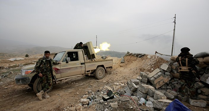 Kurdish peshmerga fighter fires a weapon towards positions of the Islamic State group who are 500 meters or half a mile away, overlooking the strategic town of Sinjar, northern Iraq