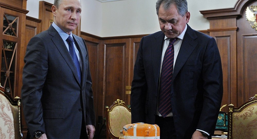 Russian Defense Minister Sergei Shoigu shows President Vladimir Putin a flight recorder of a Russian warplane shot down by a Turkish jet on Nov. 24.