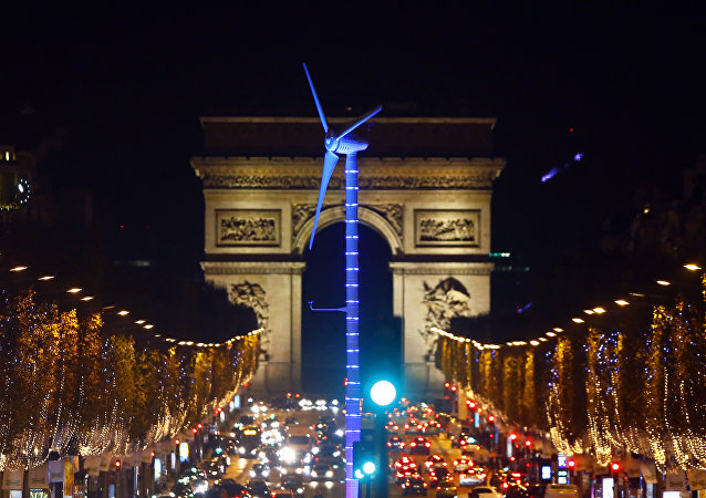 A power-generating windmill turbine is seen on the Champs Elysees avenue with the Arc de Triomphe in background as part of the COP21, United Nations Climate Change Conference, in Paris, Wednesday, Dec. 2, 2015