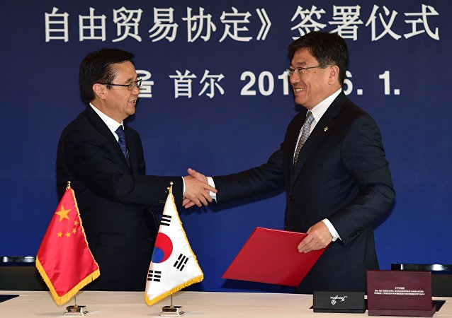 Chinese Commerce Minister Gao Hucheng (L) shakes hands with South Korean Trade Minister Yoon Sang-Jick (R) during a signing ceremony for a bilateral free trade agreement at a hotel in Seoul on June 1, 2015