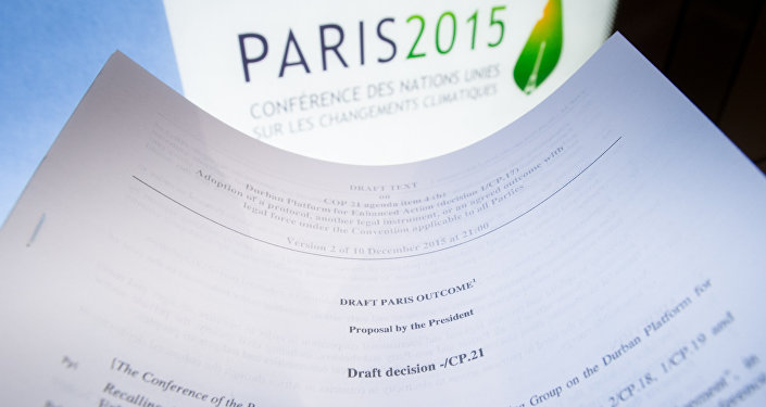 An illustration picture taken on December 10, 2015 in Paris shows a draft for the outcome of the COP21 United Nations conference on climate change next to the logo of the summit