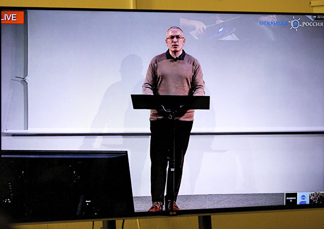 Mikhail Khodorkovsky, once Russia's richest man, speaks during a webcast conference in London, and is seen on a TV screen in Open Russia movement office in Moscow, Russia, on Wednesday, Dec. 9, 2015