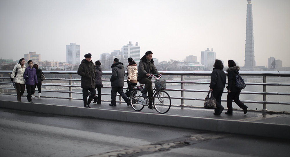 North Koreans walk along a bridge that takes them over the Taedong River on Wednesday, Dec. 2, 2015, in Pyongyang, North Korea. Seen in the background is the Juche Tower
