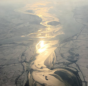 In this Friday, Nov. 27, 2015, photo, which was taken from an airplane approaching Pyongyang, light from the evening sun is cast on a river flowing through snow covered farm fields in North Korea