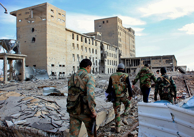 Syrian army soldiers patrol near a building previously used for storing seeds in the countryside of Deir Hafer, a former bastion of Daesh, near the northern Syrian city of Aleppo on December 2, 2015