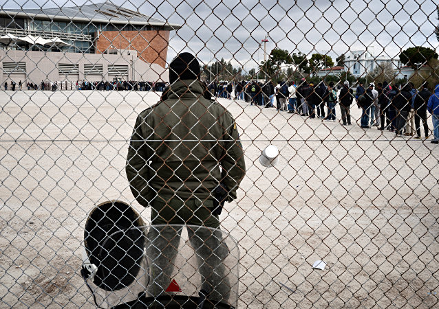 A riot policeman stands guard at a temporary housing facility for migrants nad refugees located in a former Olympic hall in Faliro suburb of Athens on December 11, 2015.