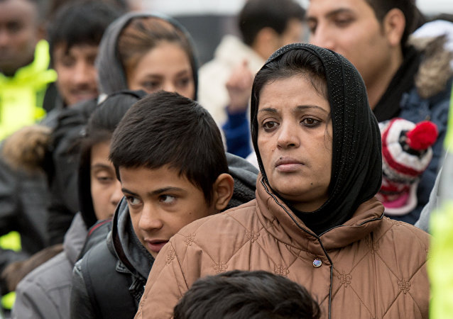 Migrants wait for registration at the Hesse state Initial Reception Center in Giessen, Germany, Wednesday Dec. 2, 2015.