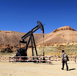 A Libyan security member walks by an oil drill on March 23, 2013 at the al-Ghani oil field, near the city of Waddan in the central Al-Jufrah province.