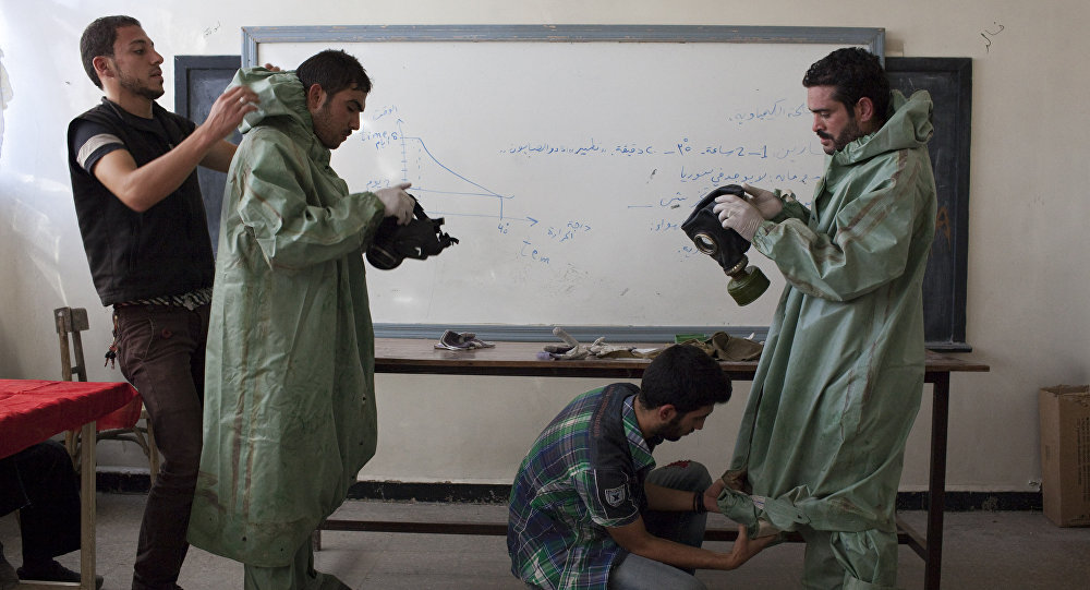 Aleppo University student, shows Syrian citizens hows to put protective gear as he instructs them with rudimentary means of how to respond to a chemical attack, in the northern Syrian city of Aleppo . file photo