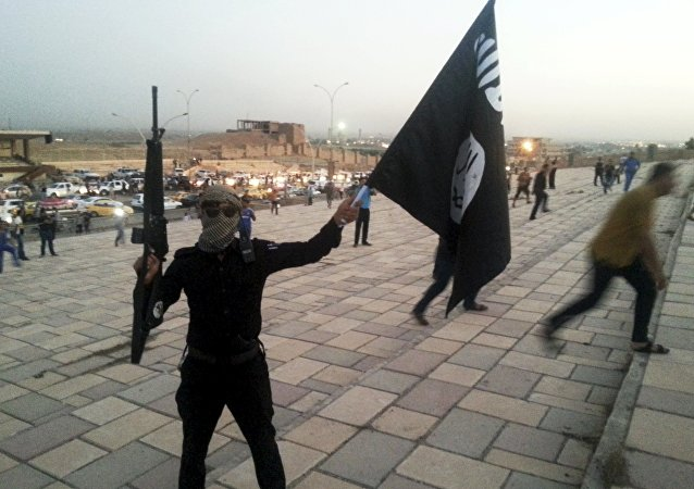 A fighter of Daesh holds a Daesh flag and a weapon on a street in the city of Mosul, Iraq, in this June 23, 2014.