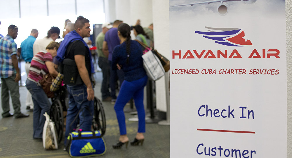 Travelers line up to check in for charter flights from Miami to Havana at Miami International Airport, Friday, Jan. 16, 2015 in Miami