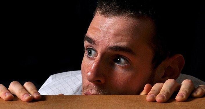 A man hiding behind a desk
