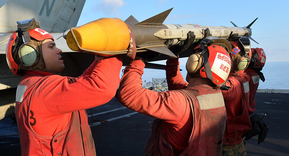 US Navy personnel load rocket on a F/A-18E Super Hornet on the flight deck of the USS Nimitz (CVN 68) aircraft carrier in the Mediterranean Sea on October 25, 2013