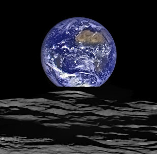The Earth straddling the limb of the Moon, as seen from above Compton crater. Center of the Earth in this view is 4.04°N, 12.44°W, just off the coast of Liberia. The large tan area in the upper right is the Sahara desert, and just beyond is Saudia Arabia. The Atlantic and Pacific coasts of South America are visible to the left. WAC E1199291151C (Earth only), NAC M1199291564LR (Earth and Moon); sequence start time 12 October 2015 12:18:17.384 UTC