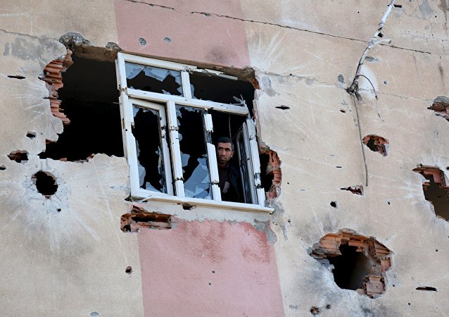 A man looks out of a building which was damaged during the security operations and clashes between Turkish security forces and Kurdish militants, in Sur district of Diyarbakir, Turkey