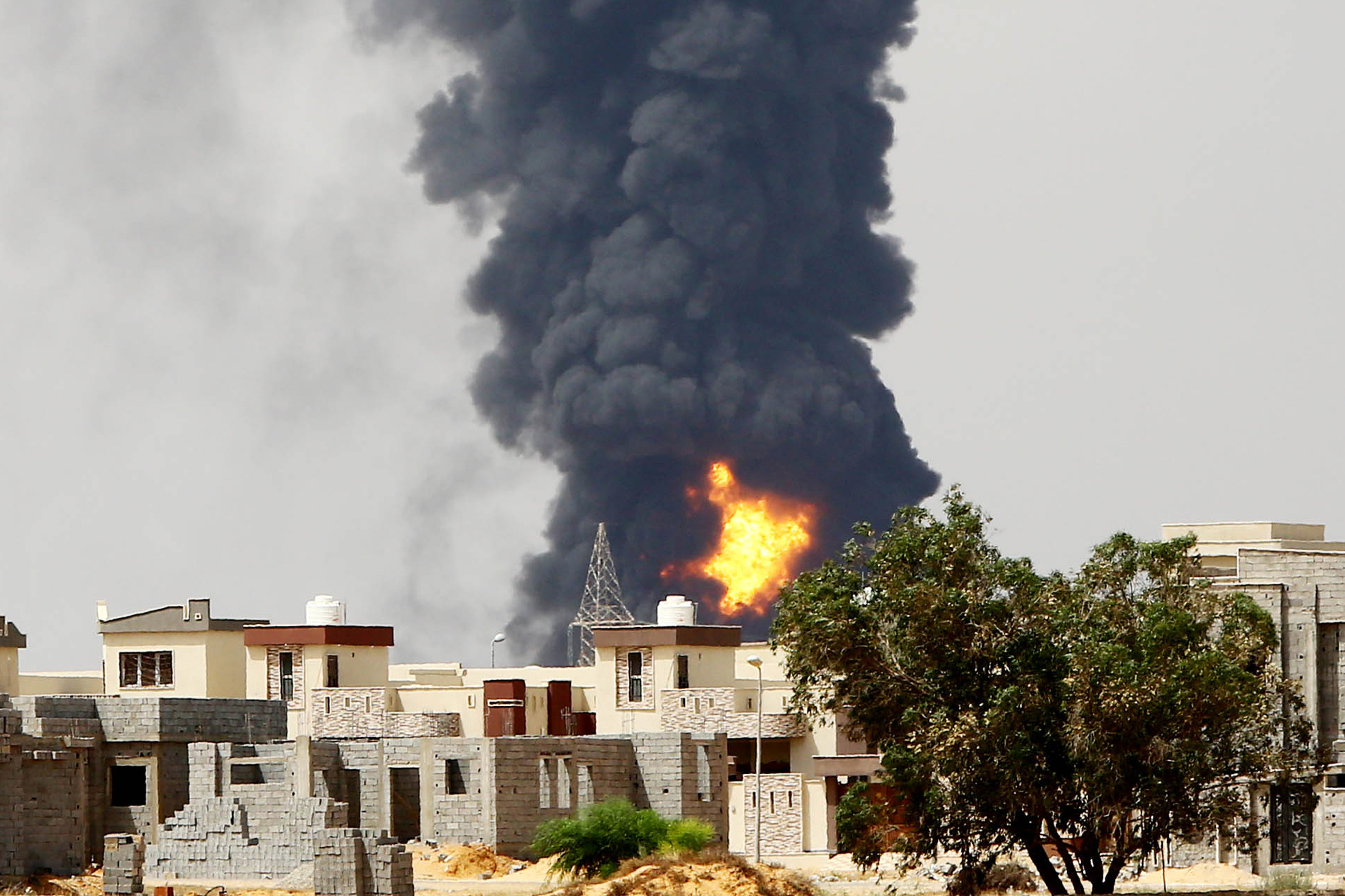 A picture taken on July 28, 2014 shows flames and smoke billowing from an oil depot where a huge blaze started following clashes around Tripoli airport, in southern Tripoli