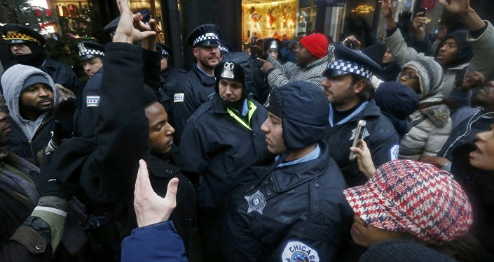 Demonstators hold their hands up in front of Chicago Police officers during protest of last year's shooting death of black teenager Laquan McDonald by a white policeman and the city's handling of the case in the downtown shopping district of Chicago, Illinois, November 27, 2015