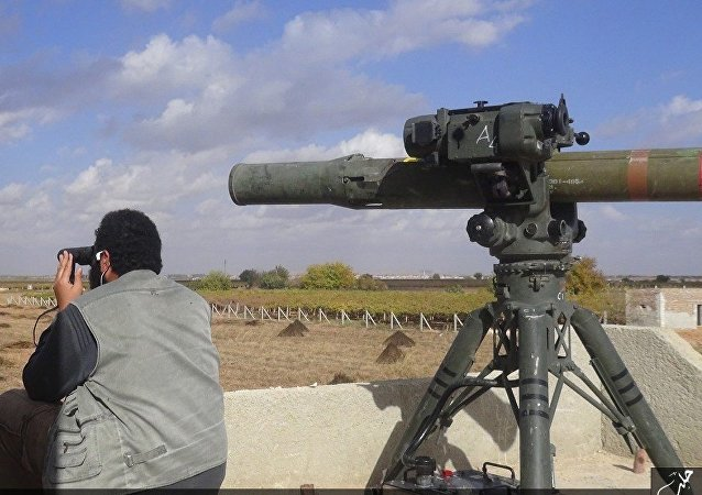In this file photo released on Dec. 21, 2015, by the Rased News Network on a page affiliated with Islamic State militants, an Islamic State militant prepares to fire a TOW-1 anti-tank missile in Aleppo, northern Syria