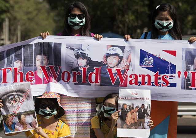 Demonstrators hold placards outside the Thai embassy in Yangon on December 26, 2015 to protest against the death sentence of Myanmar labour workers Zaw Lin and Win Zaw Tun for the murder of two British backpackers on the Thai island of Koh Tao