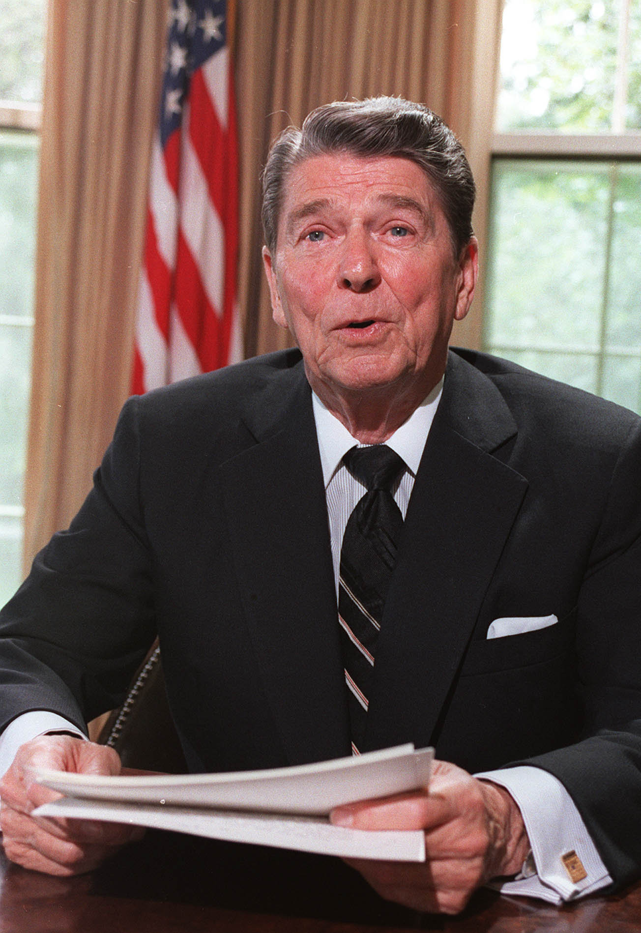 US President Ronald Reagan poses for photographers 24 June 1986 in the Oval Office at the White House, Washington,DC