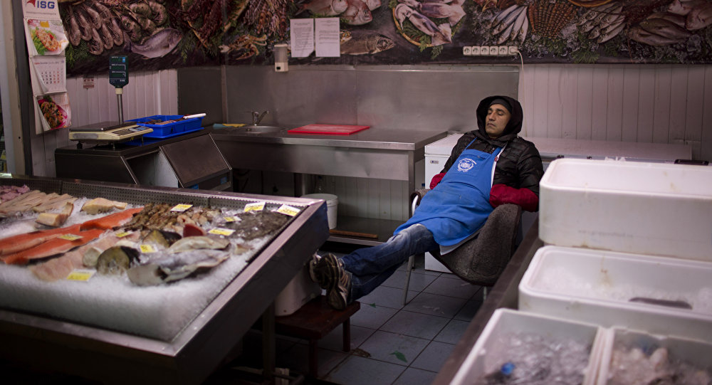 A seller sleeps inside his fish shop as he waits for customers at a market in central Kiev, Ukraine.