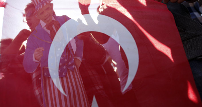 Members of Turkey Youth Union hold an effigy of U.S. President Barack Obama that is seen through a Turkish flag during a protest in Antalya, Turkey, Sunday, Nov. 15, 2015