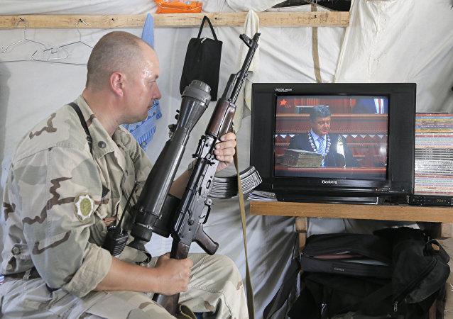 Ukrainian soldier watches the inauguration ceremony of Ukrainian President-elect Petro Poroshenko on TV in a tent at the Ukraine's Army position close to Slovyansk, Ukraine, Saturday, June 7, 2014