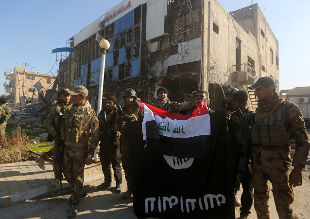 Iraqi security forces place the Iraqi flag above the Islamic State group flag as they pose for a picture on December 28, 2015 in front of the Anbar police headquarters after they recaptured the city of Ramadi, the capital of Iraq's Anbar province, about 110 kilometers west of Baghdad.