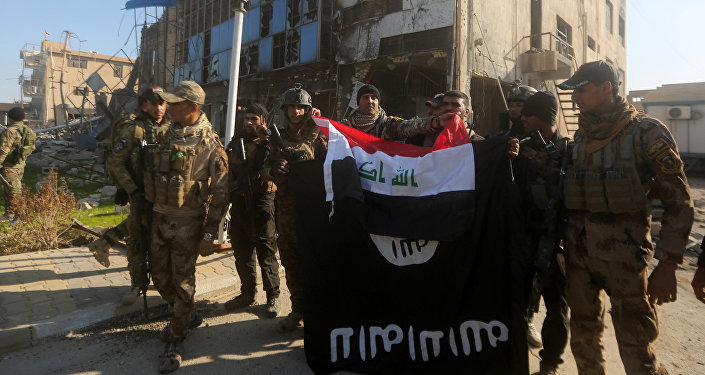 Iraqi security forces place the Iraqi flag above the Islamic State group flag as they pose for a picture on December 28, 2015 in front of the Anbar police headquarters after they recaptured the city of Ramadi, the capital of Iraq's Anbar province, about 110 kilometers west of Baghdad