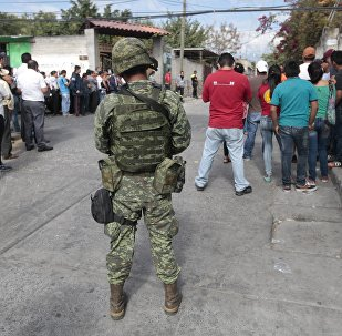 Local residents and a soldier are seen on January 2, 2016 outside the house of Gisela Mota, newly elected Mayor of Temixco, Morelos State, Mexico, murdered on Saturday at home by gunmen.