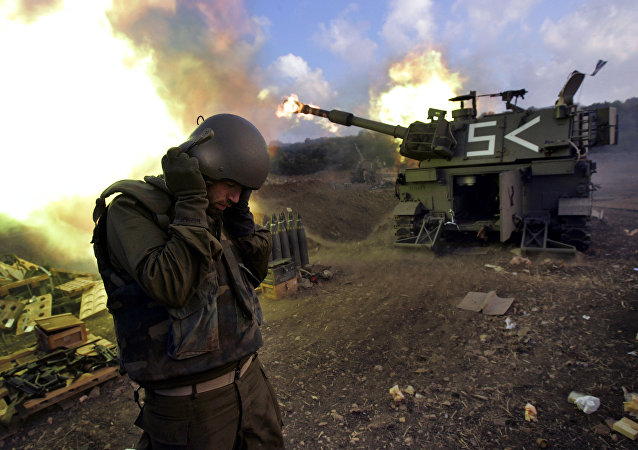 Israeli soldiers covers his ears as a mobile artillery unit fires shells into south Lebanon (File)