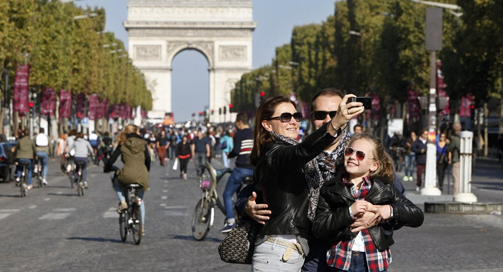 A familiy takes a selfie on the Champs-Elysees during the day without cars, in Paris, France, Sunday, Sept. 27, 2015.