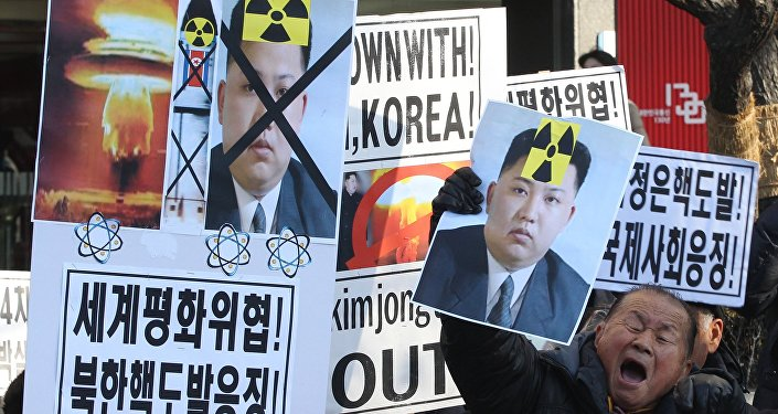 A South Korean protester with a photo of North Korean leader Kim Jong Un shouts slogans during a rally against North Korea's announcement that it had tested a hydrogen bomb.