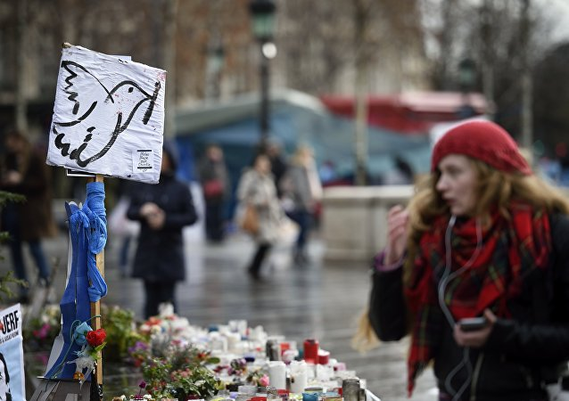 A picture taken on January 7, 2016 shows a woman standing in front of a makeshift memorial for the victims of Paris attacks at the Place de la Republique in Paris.