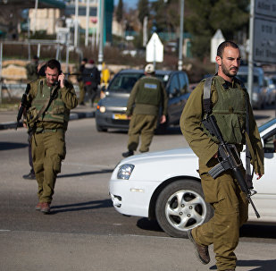 Israeli soldiers stand guard at the Gush Etzion junction in the Israeli occupied West Bank on the main road between Jerusalem and Hebron on January 5, 2016