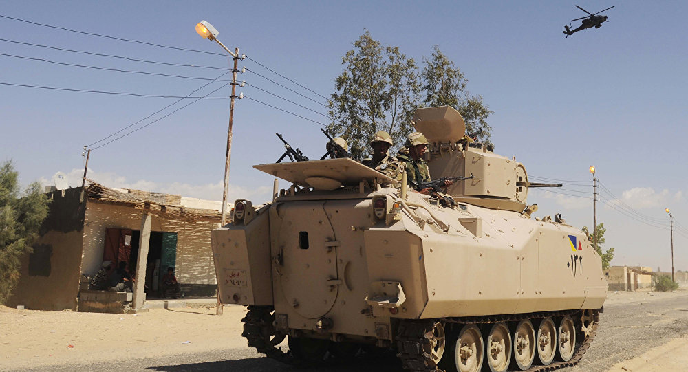 File photo, Egyptian Army soldiers patrol in an armored vehicle backed by a helicopter gunship during a sweep through villages in Sheikh Zuweyid, north Sinai, Egypt