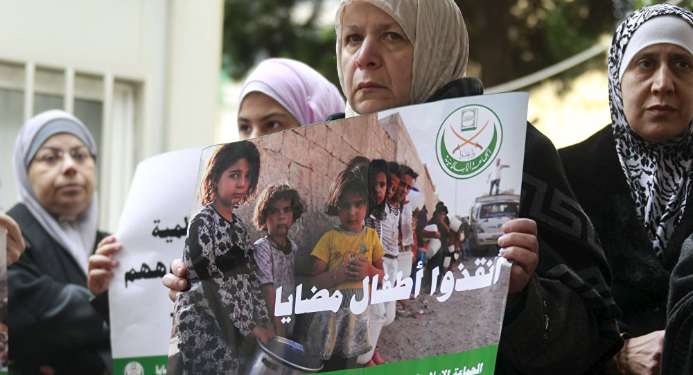 A woman holds a poster during a sit-in organized by the Sunni Al Jama'a al-Islamiya group, calling for the lifting of the siege off Madaya in front of the International Committee of the Red Cross (ICRC) in Beirut, Lebanon January 8, 2016