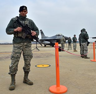 A US soldier (L) stands guard near a US F-16 fighter jet (C) and a South Korea F-15K fighter jet (R) before a press briefing on the flight by a US B-52 Stratofortress over South Korea at the Osan Air Base in Pyeongtaek, south of Seoul, on January 10, 2016