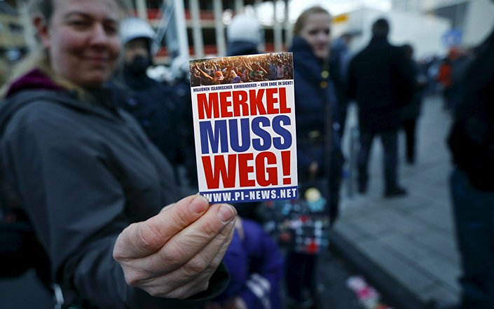 A supporter of the anti-immigration right-wing movement PEGIDA (Patriotic Europeans Against the Islamisation of the West) holds up a sticker for a photo during a demonstration rally in Cologne, Germany January 9, 2016. The sticker reads, Merkel must go!