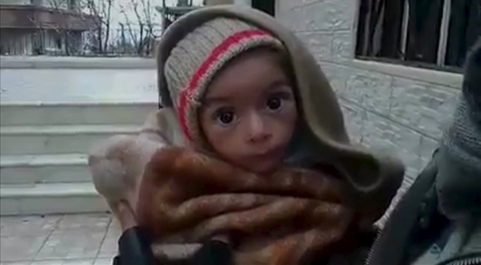 A toddler is held up to the camera in this still image taken from video said to be shot in Madaya on January 5, 2016