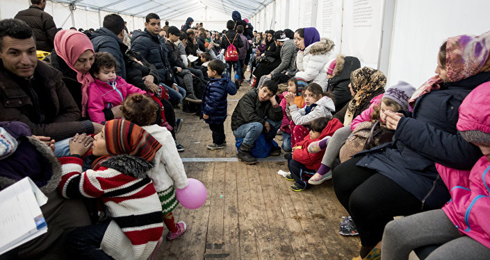 Refugees wait for their registration at the State Office of Health and Social Affairs in Berlin (LAGeSo) on November 9, 2015