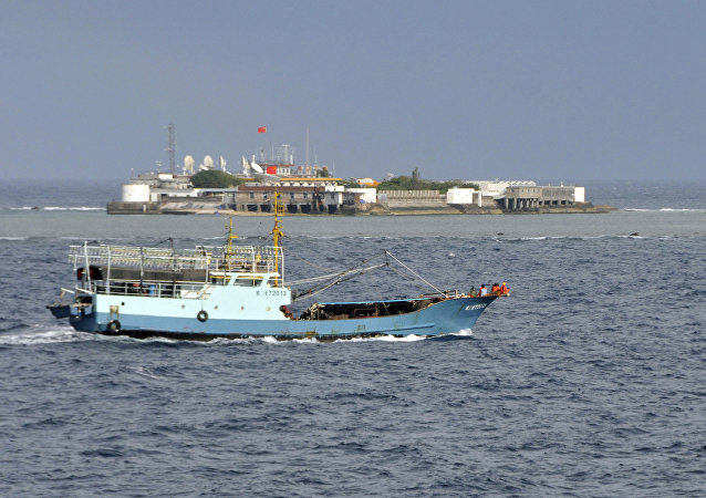 Chinese fishing vessel sails by Fiery Cross Reef, background, also known as Yongshu Reef by the Chinese, of the Spratly Islands in the South China Sea