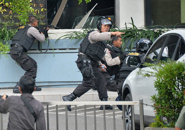 Indonesian police take position and aim their weapons as they pursue suspects outside a cafe after a series of blasts hit the Indonesia capital Jakarta on January 14, 2016