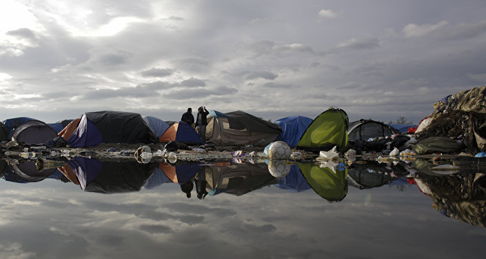 In this Tuesday, Nov. 3, 2015, file photo, tents and waste are reflected in a puddle inside the migrants camp near Calais, northern France