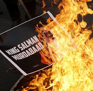 A Shi'ite Muslim burn a picture of Saudi King Salman bin Abdulaziz