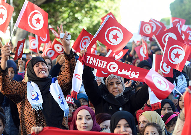 Tunisian women wave national flags and shout slogans on January 14, 2016, during a rally on Habib Bourguiba Avenue in Tunis to mark the fifth anniversary of the 2011 revolution.